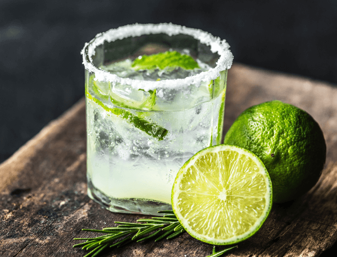 A Mojito cocktail with a sugared glass rim next to freshly cut limes