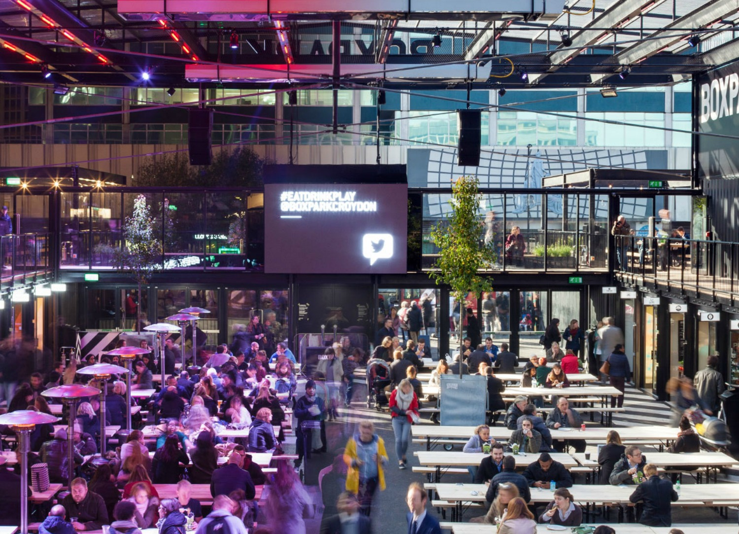 The inside of Boxpark in Croydon with people sat down